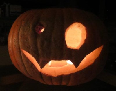 Photo of a selfcarved pumpkin with a small and a large eye and a grin with two canine teeth