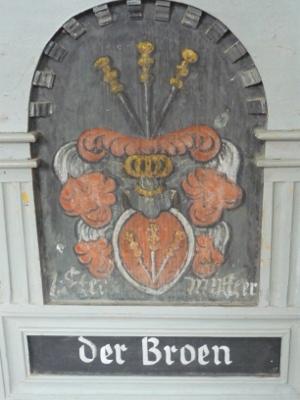 Der Coat of Arms: Drei Speere spießen in einen Helm, der auf einem Schild mit ebenfalls drei Speeren ruht. Daneben Federn