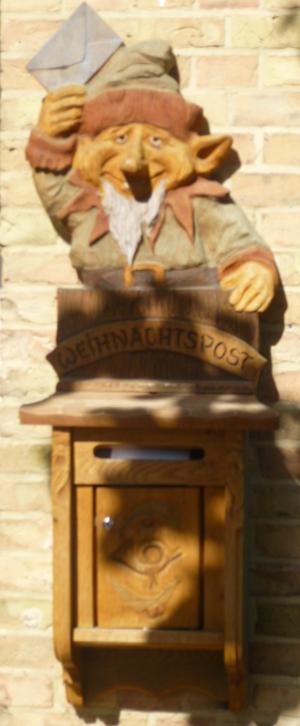 Briefkasten für Weihnachtsmann-Post. Über dem hölzernen Kasten sitzt ein geschnitzter Elf, der freudig einen Brief in die Höhe hält.