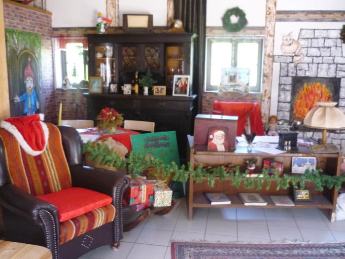 Ein Blick in die Weihnachtsmannstube. Ein gemütlicher Sessel und jede Menge Weihnachtskram vor einem angemalten Kamin.