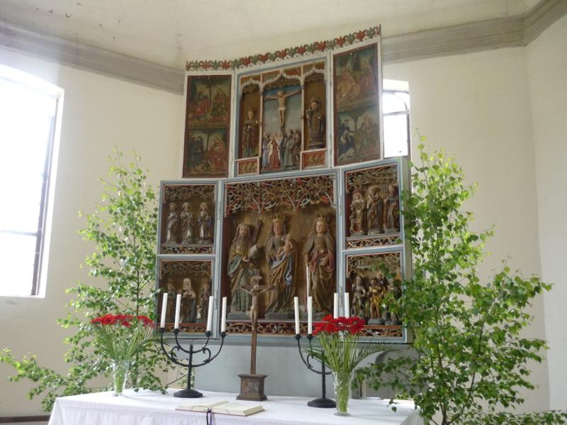 Das Altarbild. Mehrere kleine Fenster mit unterschiedlichen Figuren, inklusive eines Kreuzigungsmotivs in der Mitte
