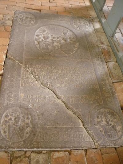 Eine der Grabplatten. Die eingeritzte Schrift ist nur noch schwer lesbar. Ein Riss spaltet sie an der unteren linken Ecke