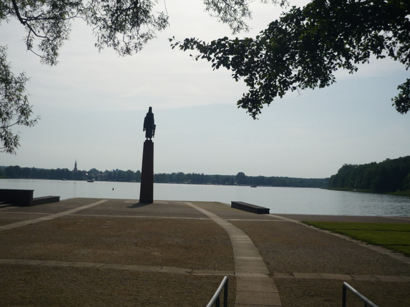 A view towards Fürstenberg. A statue is standing on a cobbled ground before the lake.