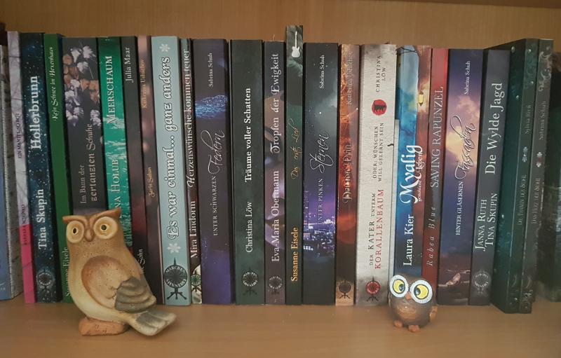 Die unten genannten Bücher nebeneinander (Buchrücken). Davor zwei Eulenfiguren, links eine kleine, rechts eine winzige mit übergroßen Augen.