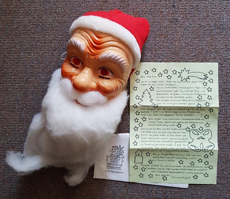 Plaste-Weihnachtsmann Larve mit Wattebart und roter Mütze. Daneben ein grüner Brief mit nachgezeichneten Sternen und Motiven und ein Umschlag mit Stempel von HImmelpforten
